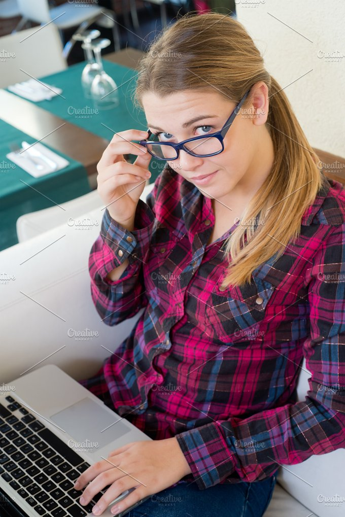 young girl with laptop looking at camera in the bar.jpg - Technology