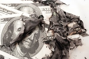 burned dollar bills on white backgro