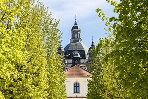 Baroque monastery through green tree
