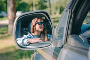 Woman reflection in side view mirror