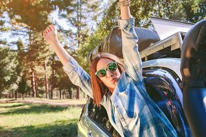 Happy woman raising arms out of car