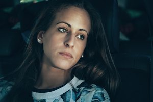Sad young woman girl crying in car