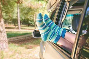 Girl legs with socks over window car