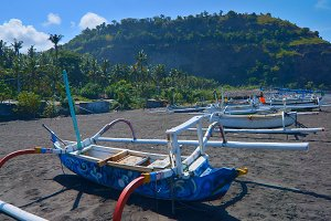 Local  boats on the beach of black sand on the island of Bali in Indonesia.jpg
