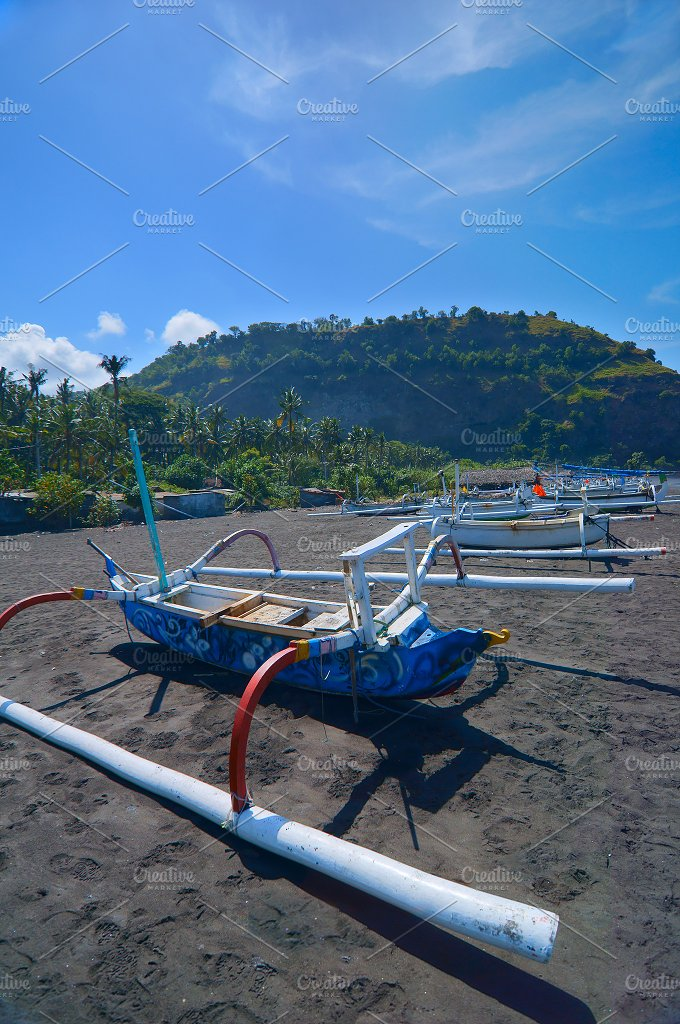Local boats on the beach of black sand on the island of Bali in Indonesia.jpg - Nature