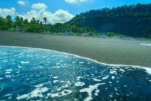 Boats on the beach of black sand on the island of Bali in Indonesia in sunny summer day.jpg