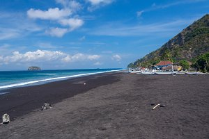 Junks on the beach of black sand on the island of Bali in Indonesia. Summer sunny day..jpg