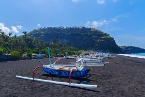 Junk on the beach of black sand on the island of Bali in Indonesia.jpg