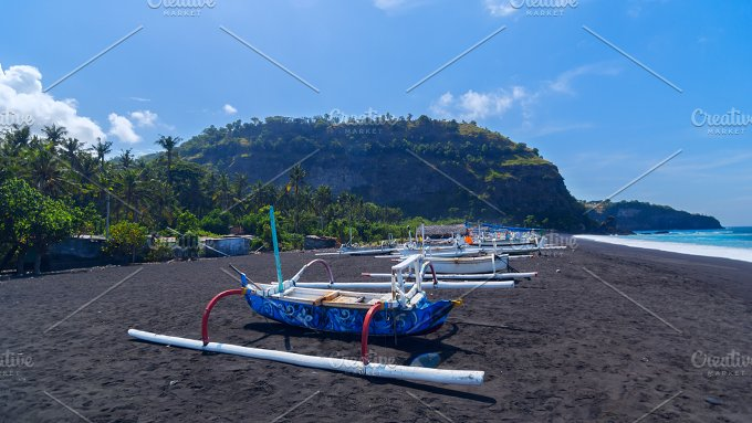 Junk on the beach of black sand on the island of Bali in Indonesia.jpg - Nature