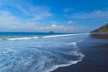 The beach with black volcanic sand on the island of Bali in Indonesia on a sunny summer day..jpg