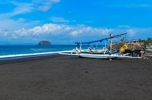 Junks on the beach of black sand on the island of Bali in Indonesia.jpg