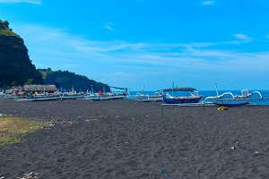 Boats on the beach of black sand on the island of Bali in Indonesia.jpg