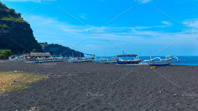 Boats on the beach of black sand on the island of Bali in Indonesia.jpg - Nature