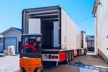 Worker on the loader loads long white semi-trailer.jpg