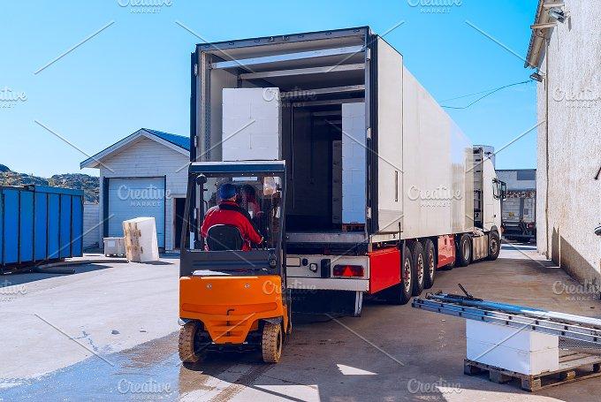 Worker on the loader loads long white semi-truck.jpg - Transportation