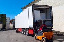 Worker on the loader loads white semi-truck.jpg