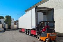 Worker on loader loads white semi-truck.jpg