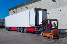 Worker on the loader unload white semi-trailer.jpg