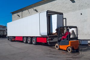 Worker on the loader unload white semi-trailer.jpg
