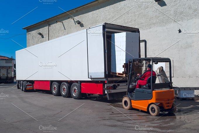 Worker on the loader unload white semi-trailer.jpg - Transportation