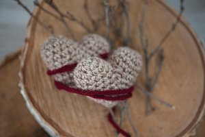 Two knrtting hearts on wooden panel