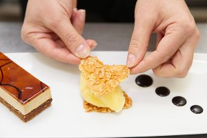 Pastry chef is decorating a dessert