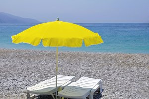 Yellow parasol and two white lounger