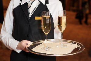 Female waiter with champagne flutes