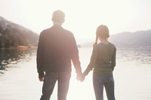 Couple holding hands near lake