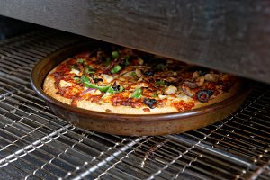 Pizza being baked in industrial oven
