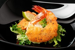 Deep fried shrimps on black plate