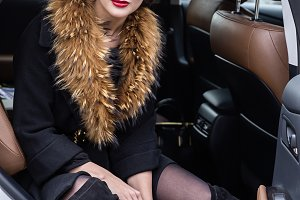 The lady in fur in the car.