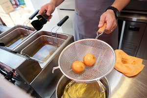 Chef cooking dish in a deep fryer