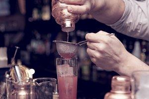 Bartender is straining cocktail