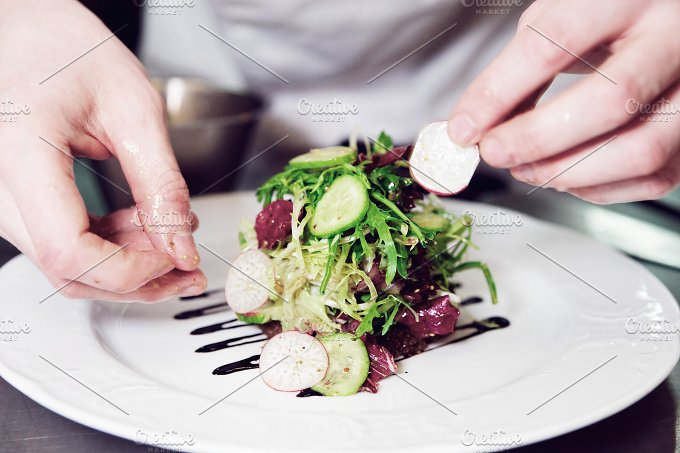 Chef is decorating appetizer, toned - Photos