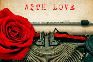 Typewriter and red rose flower