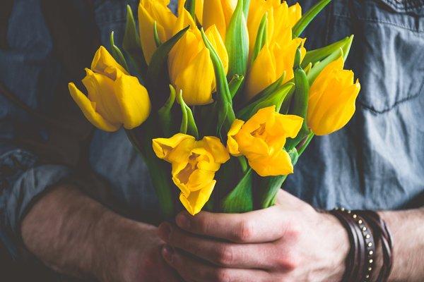 Man holding yellow tulips