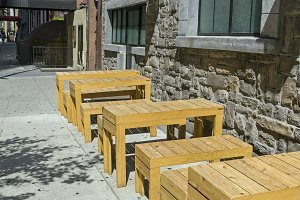 Wooden tables on a city street.