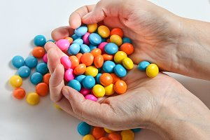 Colored candies in hands