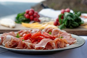Platter with cured ham on table