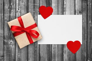 Paper with gift box and red hearts