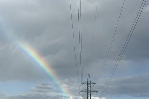 Electric line, clouds and rainbow