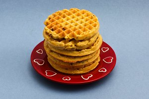 Red plate with six blueberry wafles