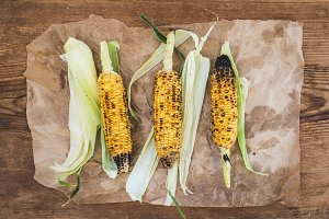 Grilled corn over oily craft paper