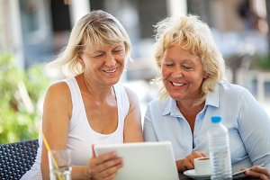 Two women friends using tablet