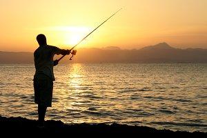 Man fishing in last rays of sunlight