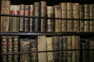 Antique books on wooden shelves 2