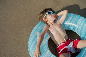 Boy lying in the seashore relaxed