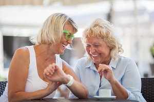 Senior women laughing in street cafe