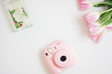 Desk, pink Instax & flowers, perfume